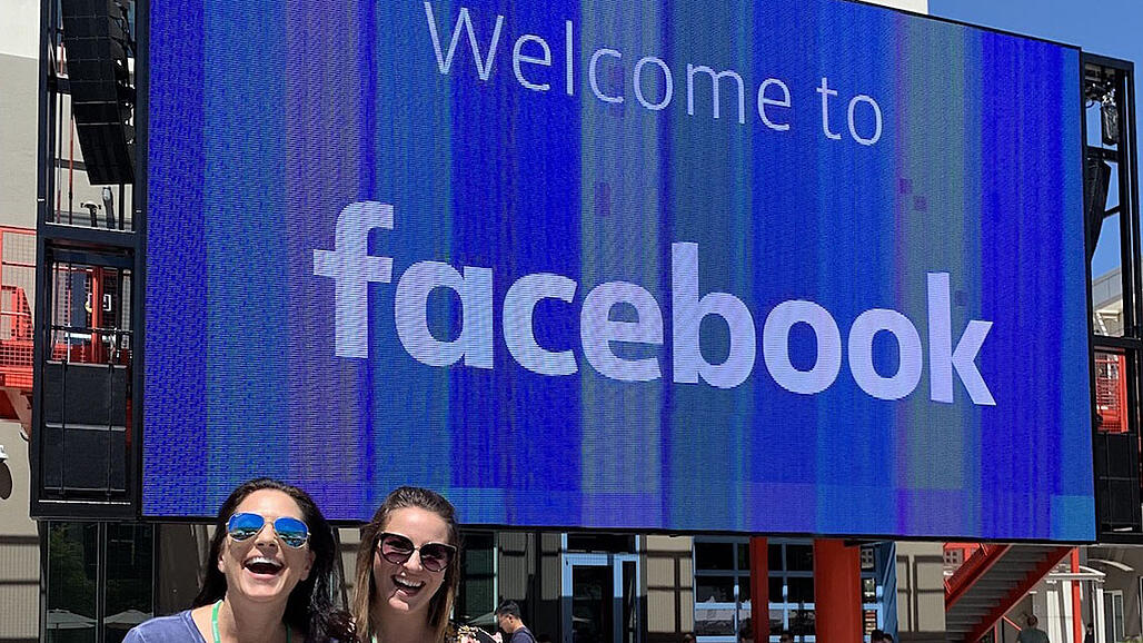 """VMG Studios CEO and founder Kelly Sparks and VP of Key Accounts Alysia Lee stand outside Facebook headquarters next to """"Welcome to Facebook"""" sign"""