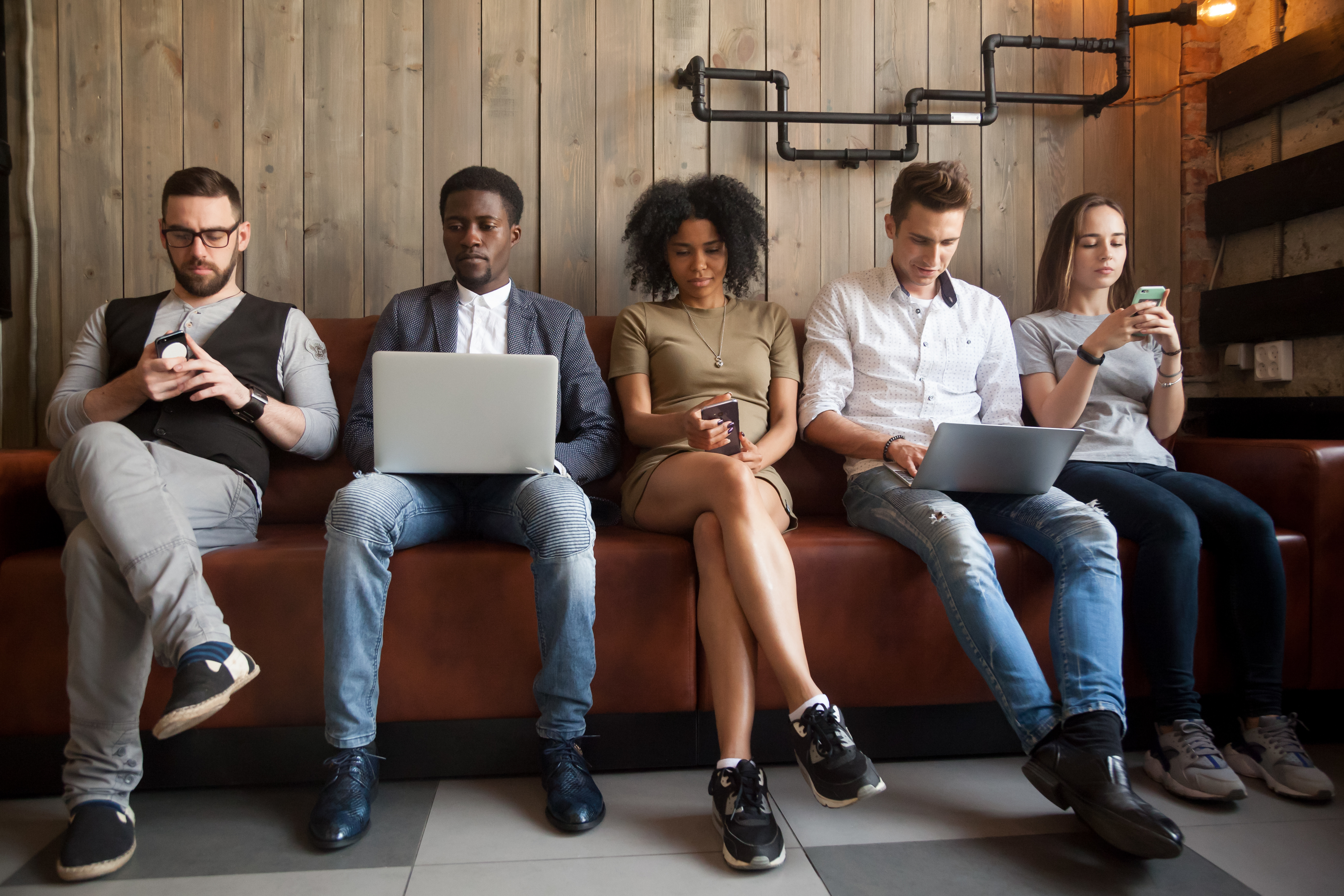 5 millennials sitting on a bench on various electronic devices such as smartphone and laptops