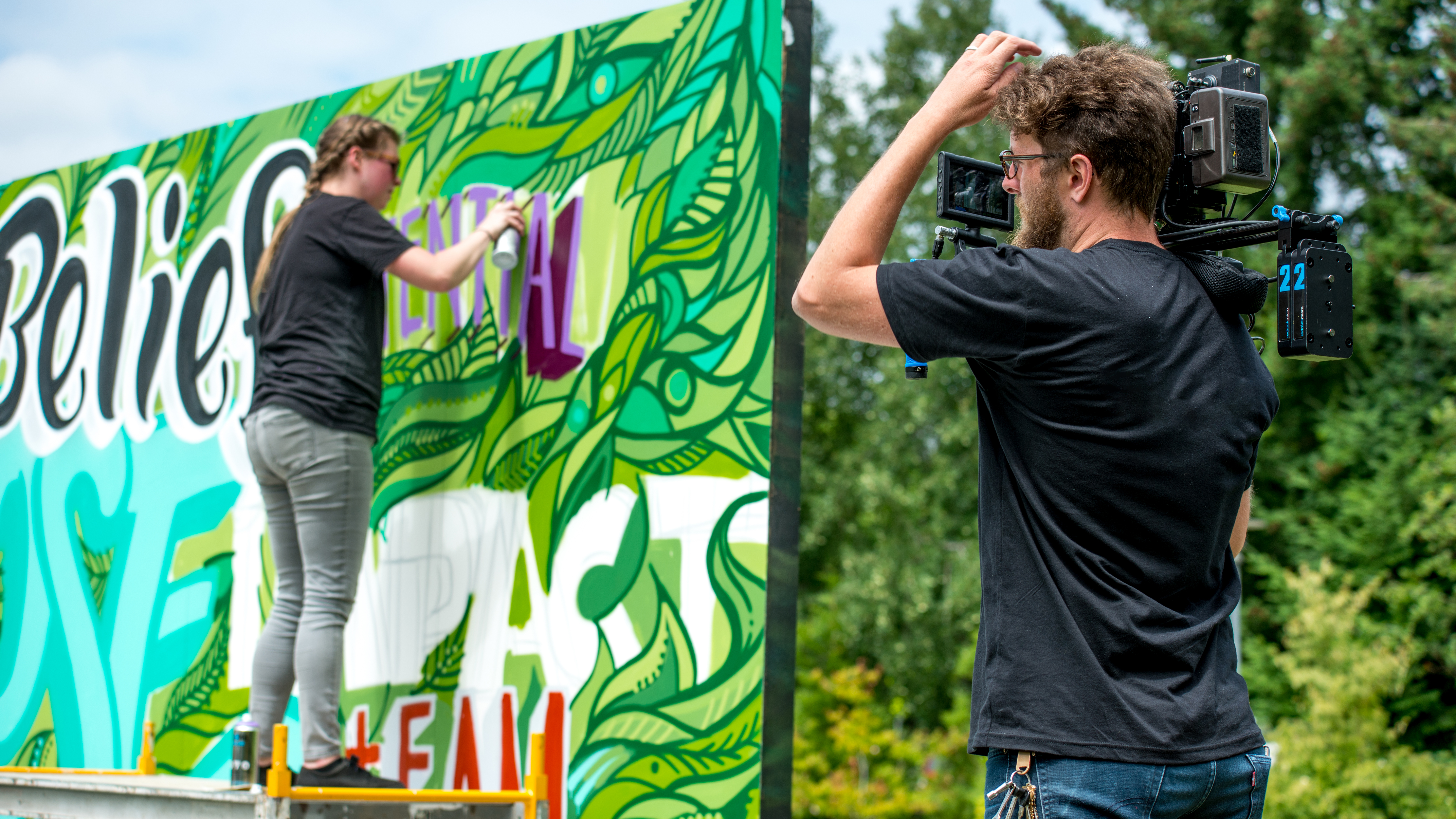 Director of Photography/camera operator on video production set filming a person painting a graffiti wall outside.