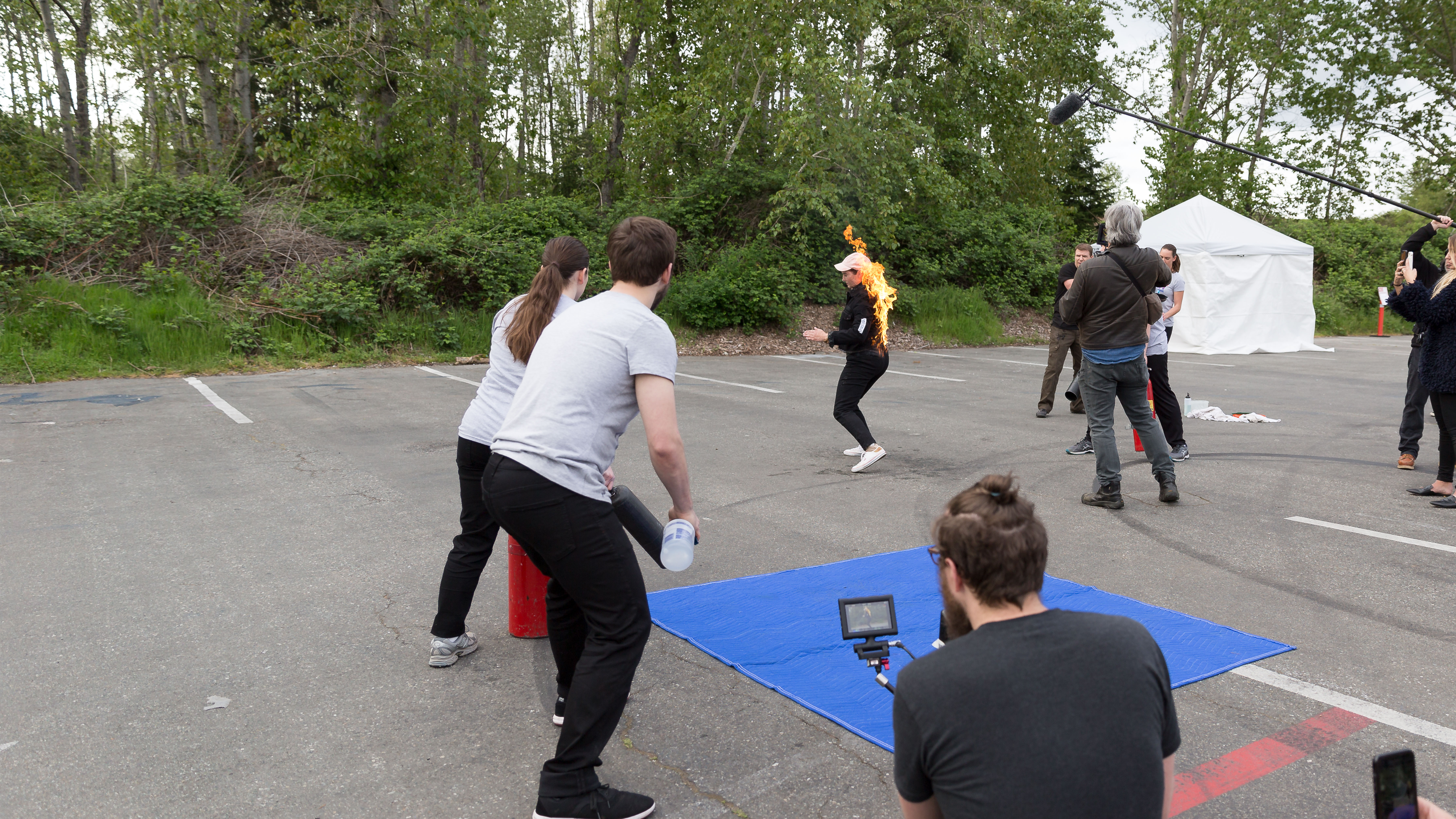 Video production crew filming a stunt school of a woman on fire