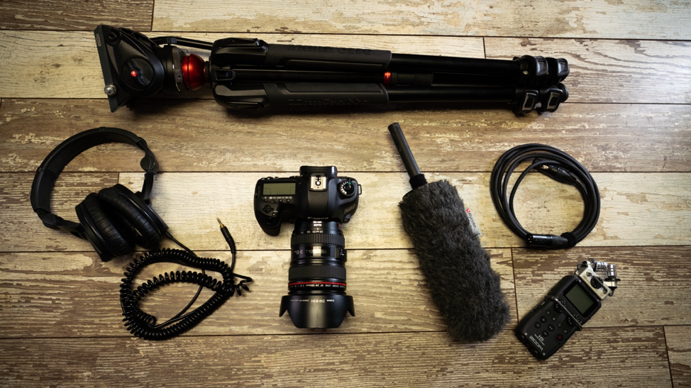 Video production equipment pack including a tripod, camera, microphone, audio recorder, headphones and audio cable
