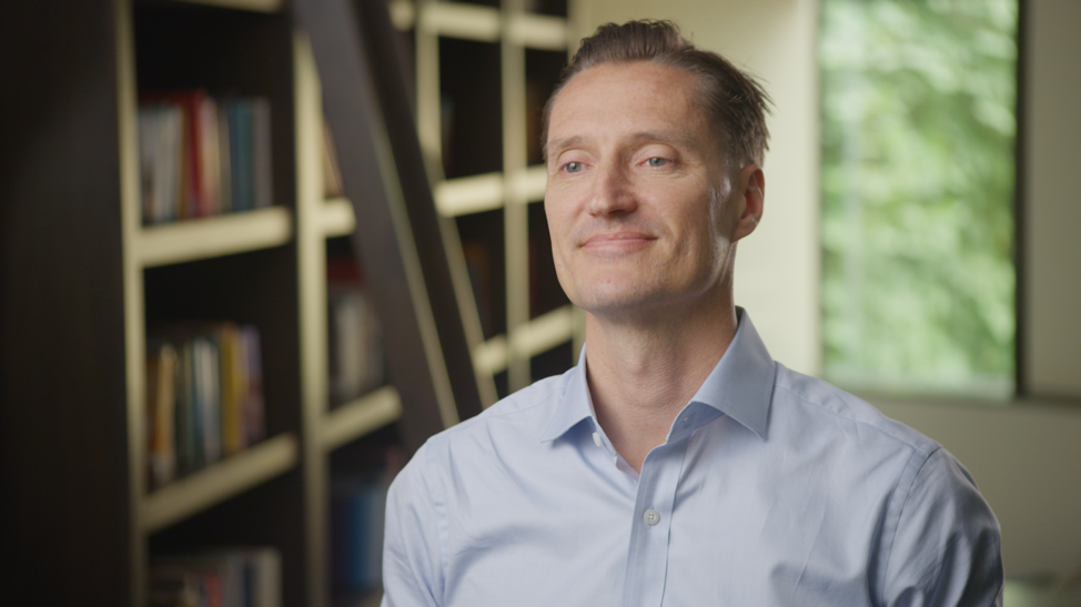 Middle-aged man sitting in library setting looking off camera in organic setting