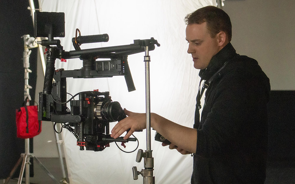 Assistant camera preps the camera on a stabilizer and tests a wireless follow focus