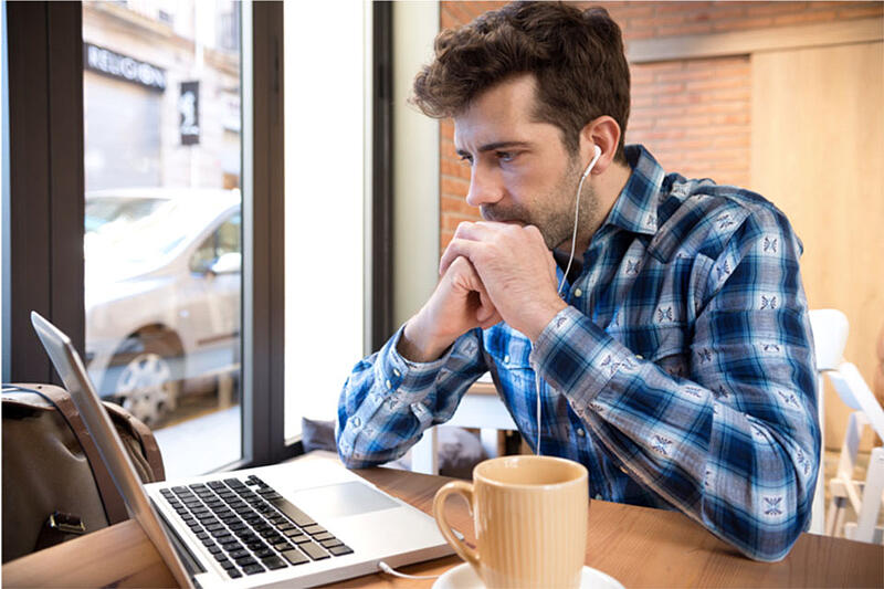 Man wearing headphones watching video on his laptop in a coffee shop setting