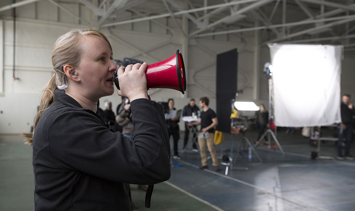 Woman serving as an assistant director holding a megaphone calling for another take on a video production shoot in a warehouse setting