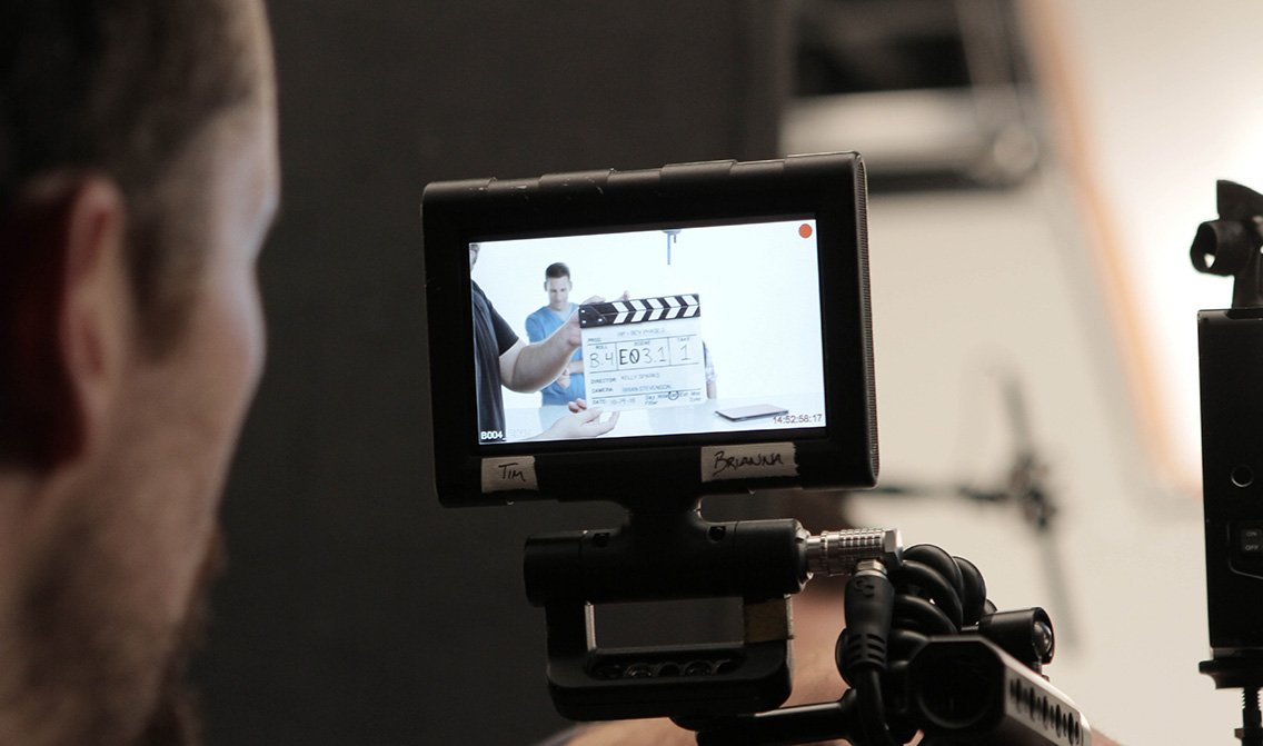 Camera operator looks at video monitor before rolling on set during a video production shoot at VMG Studios