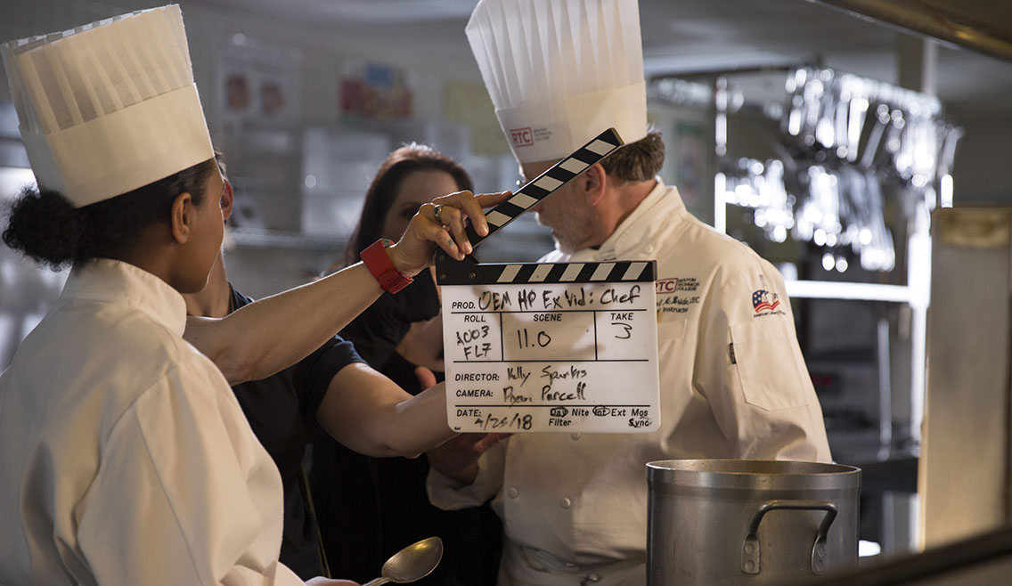 Production assistant holds up a slate for a video production shoot featuring on-camera talent as chefs