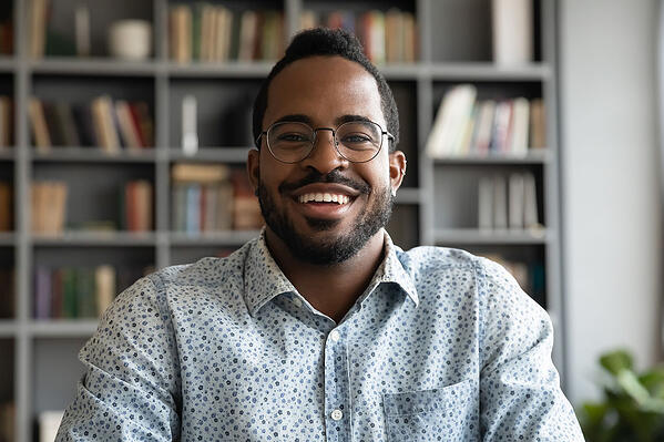 Man wearing glasses smiling at a webcam with a bookcase in the background