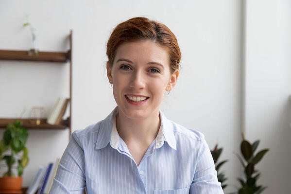 Woman smiling at webcam with a clean, white background