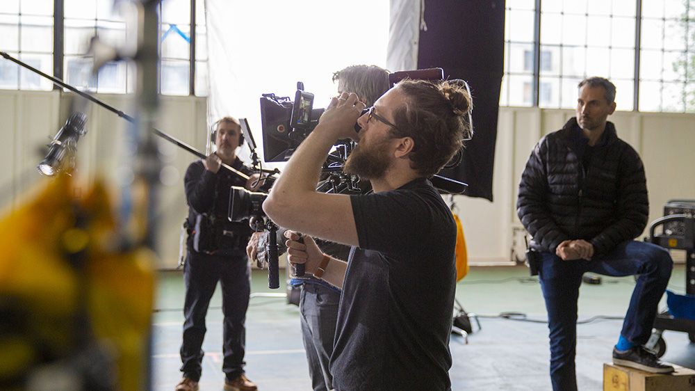 Male camera operator filming on a video production set with a boom operator and another man in the background of a warehouse setting