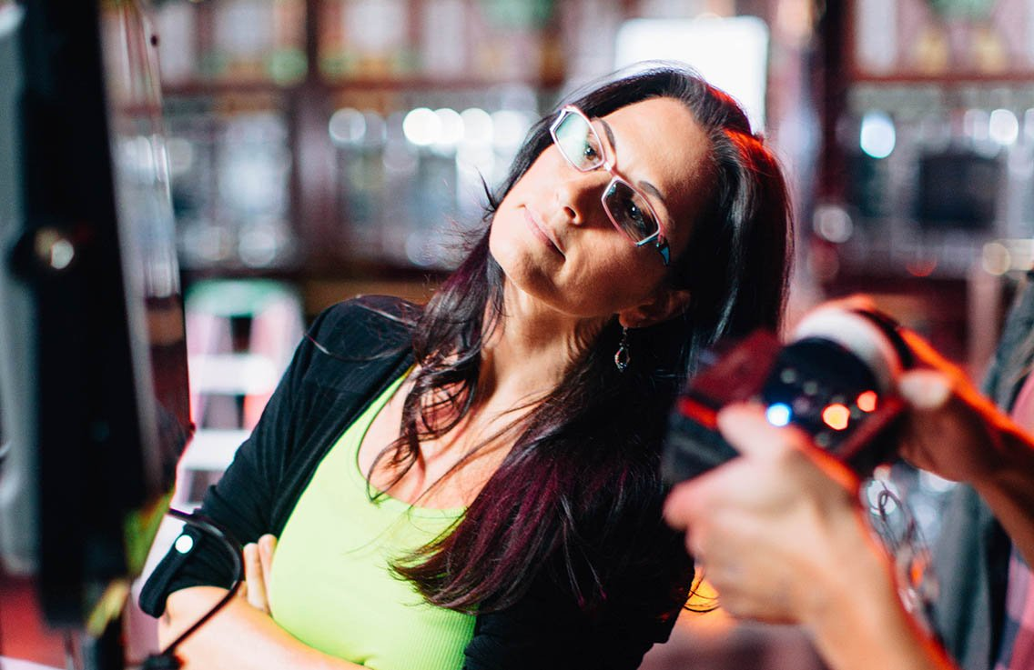 Female director wearing glasses looking inquisitive after calling action during a video production shoot