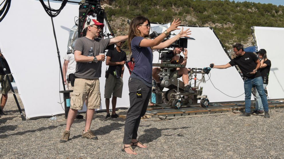 Female director Patty Jenkins directing on the set of Wonder Woman with camera crew in background