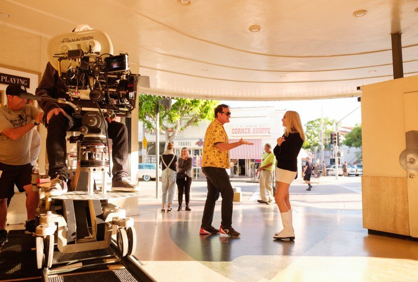 """Director Quentin Tarantino and Actress Margot Robbie talking on the set of """"Once Upon a Time in Hollywood""""."""
