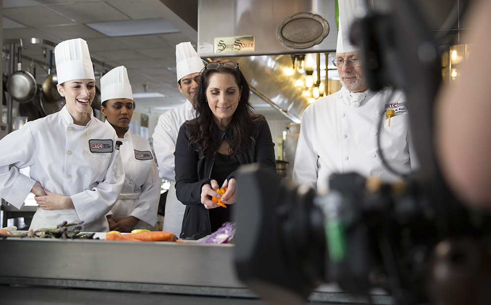 Female director walking on-camera talent dressed as chefs through their blocking and rehearsal notes in a kitchen production set