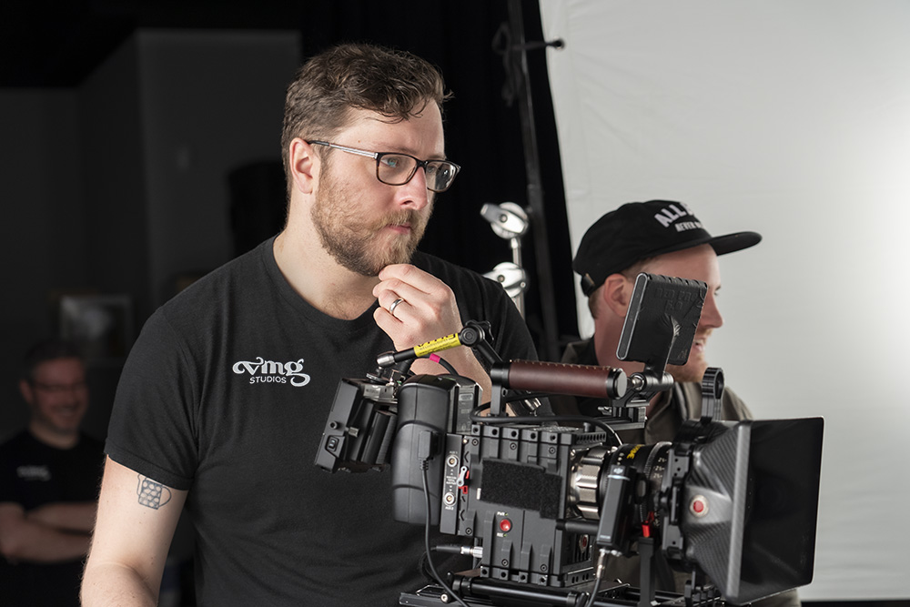 Director of Photography and cinematographer looks at his camera, considering the shot