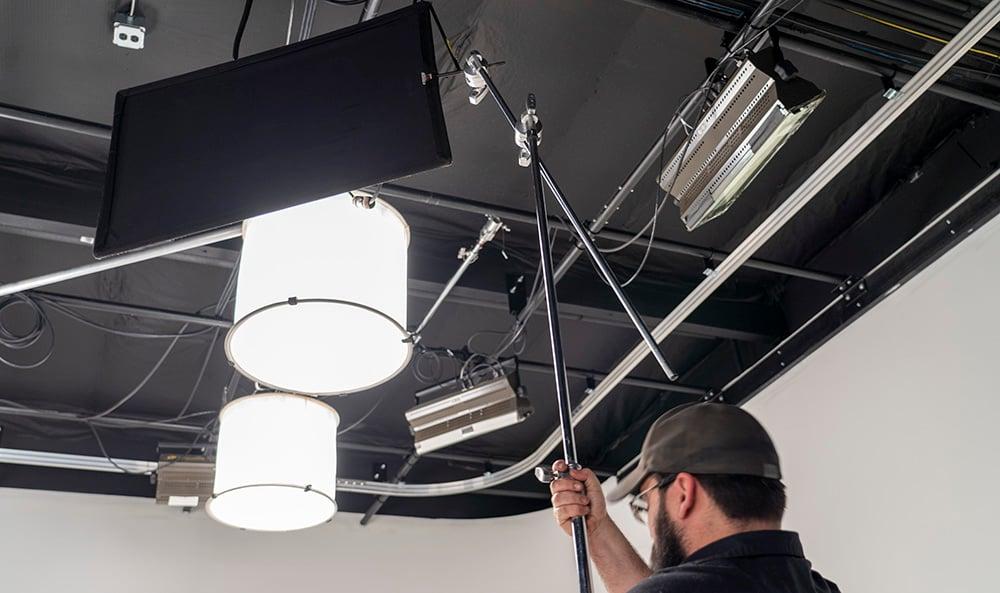 A Grip raises a flag to block light spill from a studio lamp