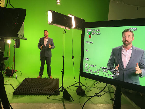 Man standing in front of a green screen in a studio in front of a camera and lights