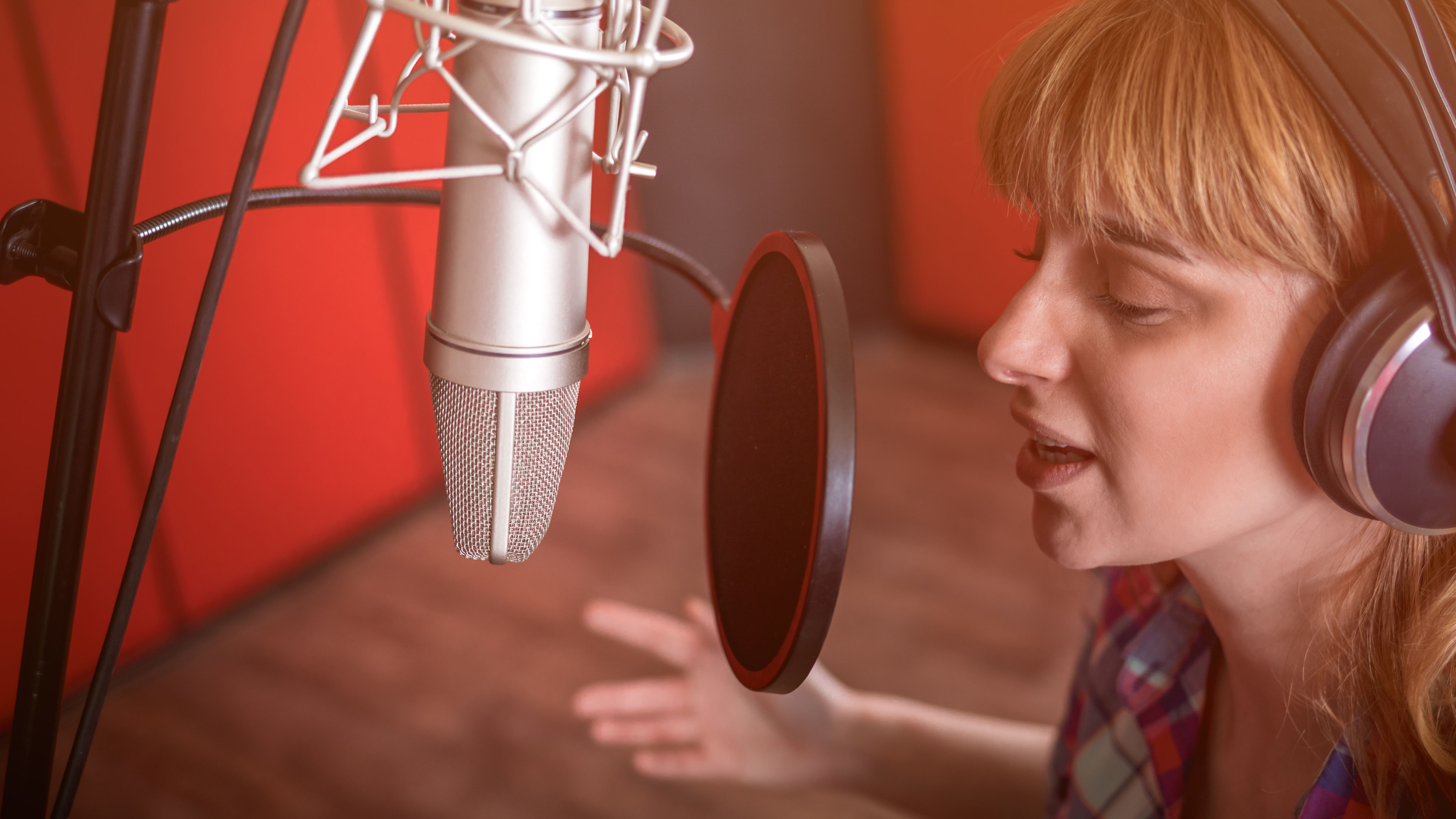 Woman recording a voice-over in an audio booth