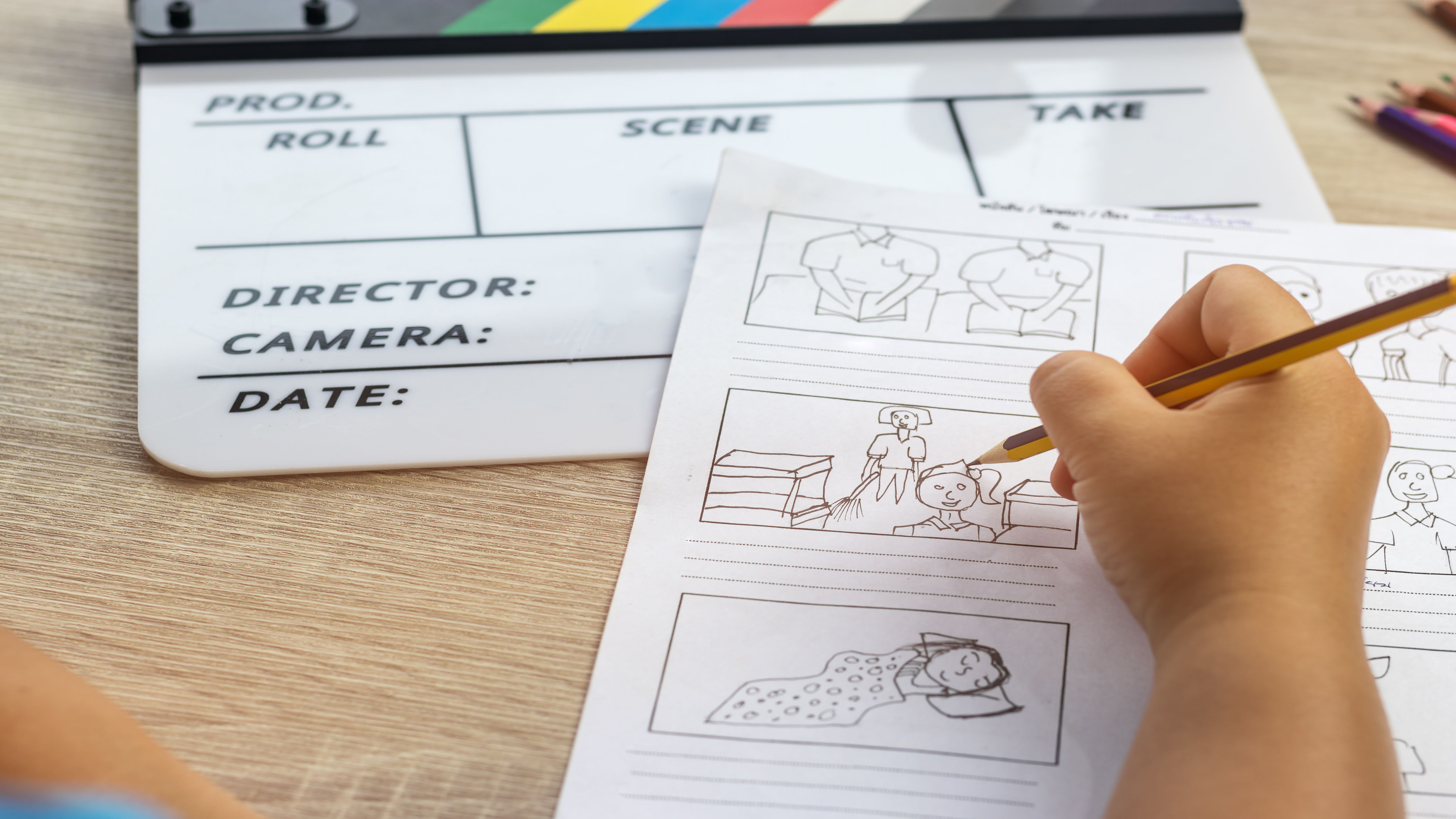 Person drawing the visual assets of a video script with a clapper board on the desk