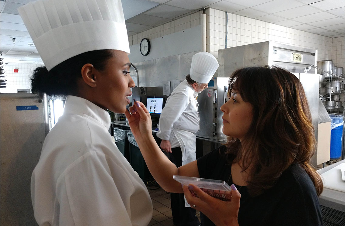 Makeup artist making final touches on the on-camera talent dressed as a chef in a kitchen setting vide production shoot