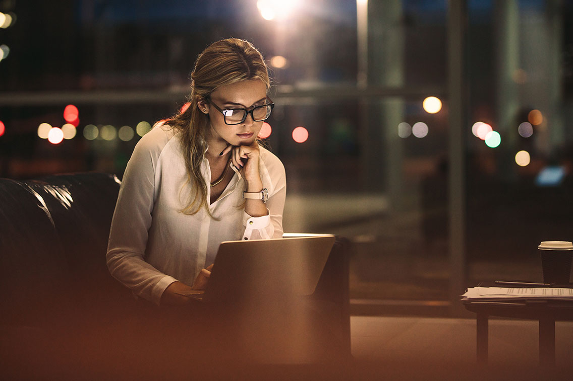 Woman wearing glasses on her computer in a dimly, warm-lit area