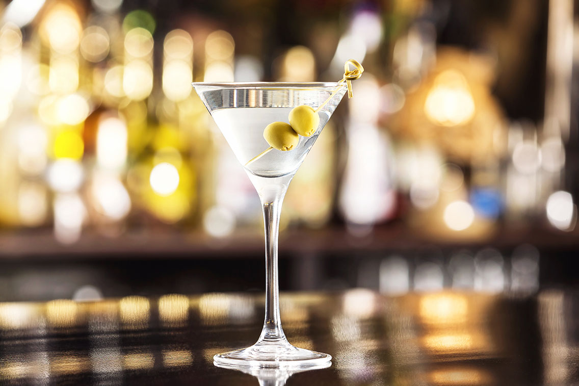 Martini glass filled with a martini and 2 olives on a toothpick in a bar setting