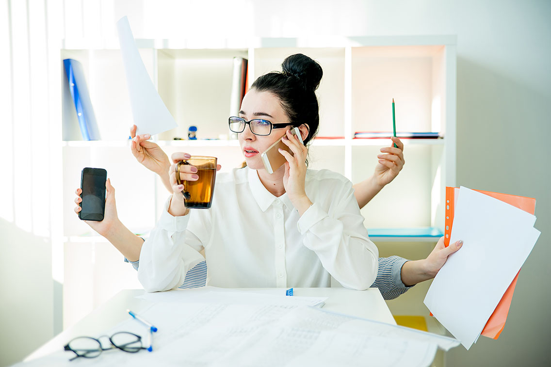Woman trying to multitask with multiple arms holding work materials like a cell phone, pencil, paperwork
