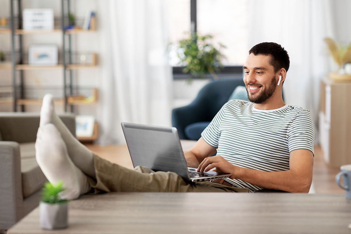 Man with airpods in listening to music while on his computer with his feet up on his clean desk workspace