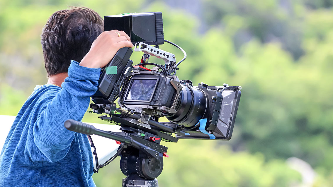 Camera operator shooting a video outside on a on-location video production set