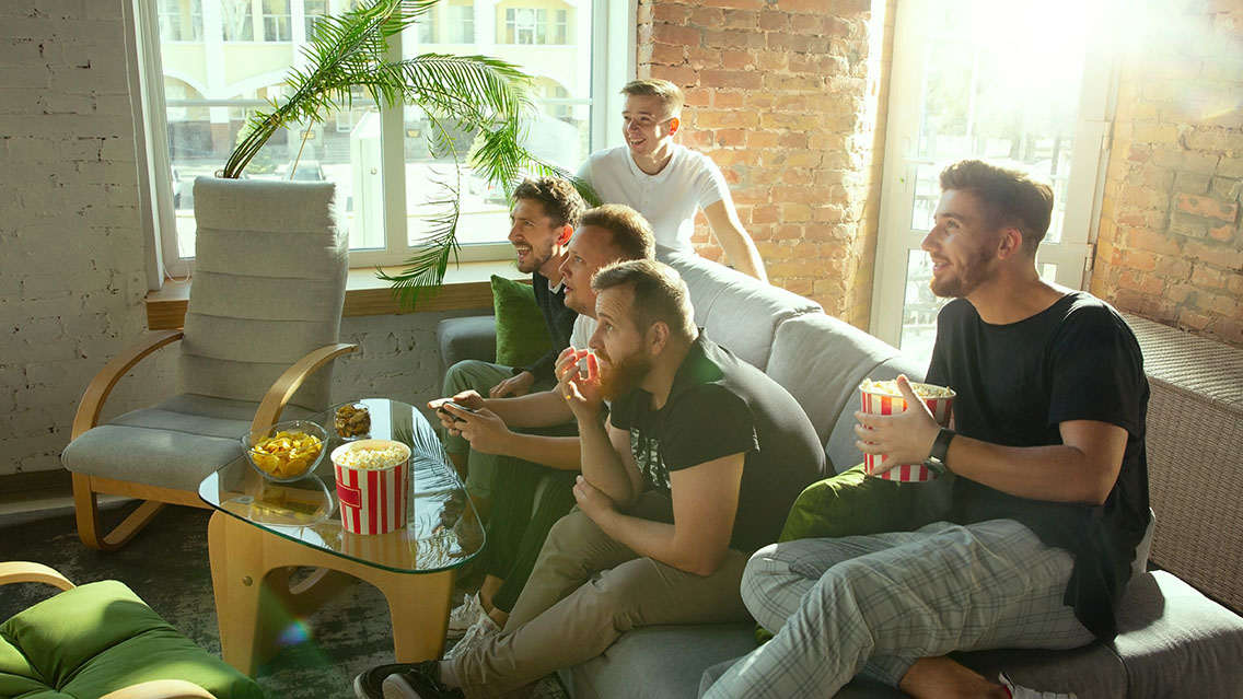 5 men in their 20s engage and watch something on a tv screen