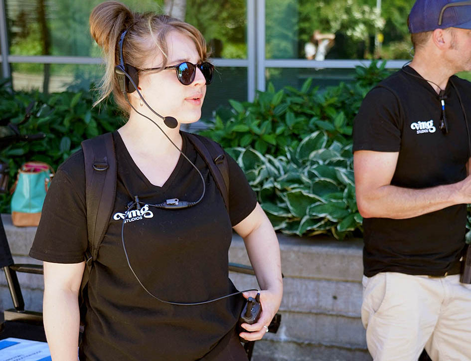 Production assistant wearing a headset and talking on a walkie-talkie during a video shoot