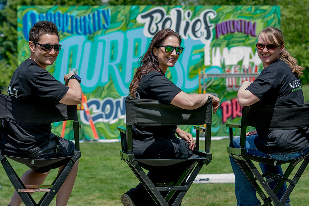 Members of the VMG Studios production team sitting on directors chairs outside in front of a graffiti wall