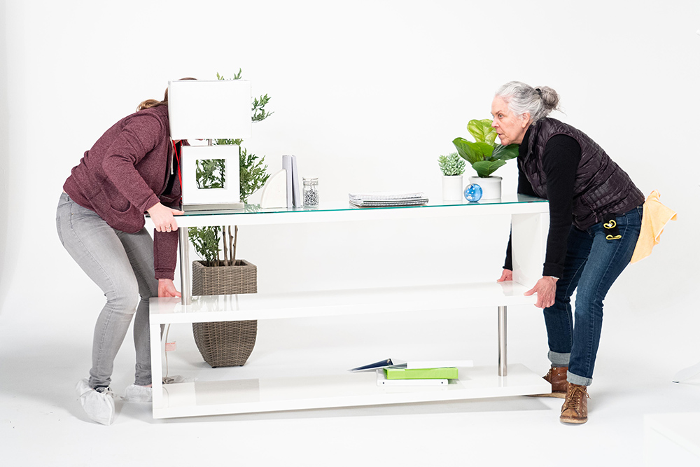 Production Designer and Set Decorator Lisa Hammond (right) arranges set pieces and dressings on set at VMG Studios. A Set Dresser assists.