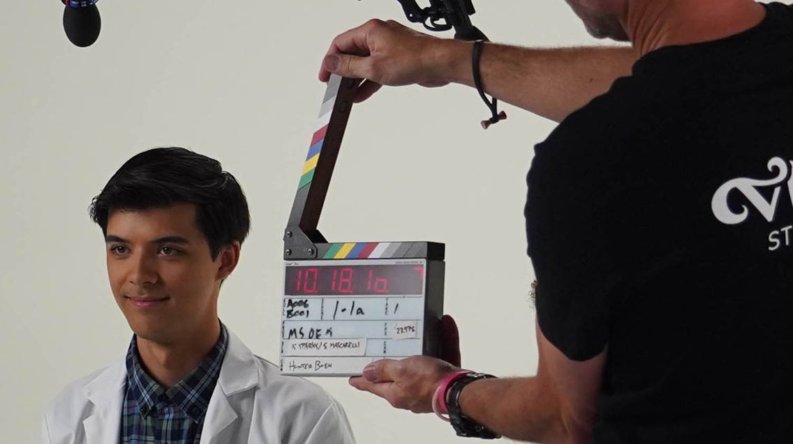 Person holds a digital clapper board with synced timecode near on-camera talent during a video production shoot in a studio