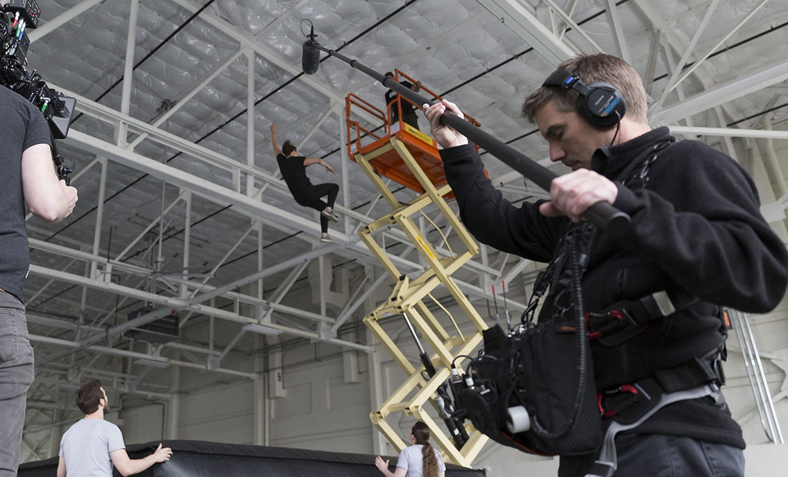 Sound tech operating the boom during a video production shoot with a woman falling from a crane in the background