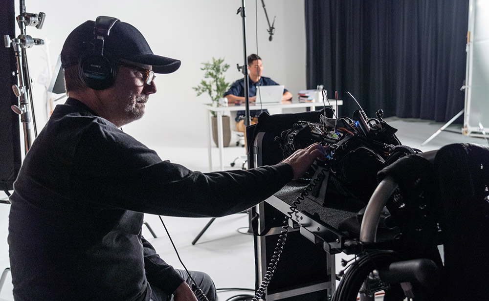 Sound mixer adjusting levels on a camera on video production shoot in a studio