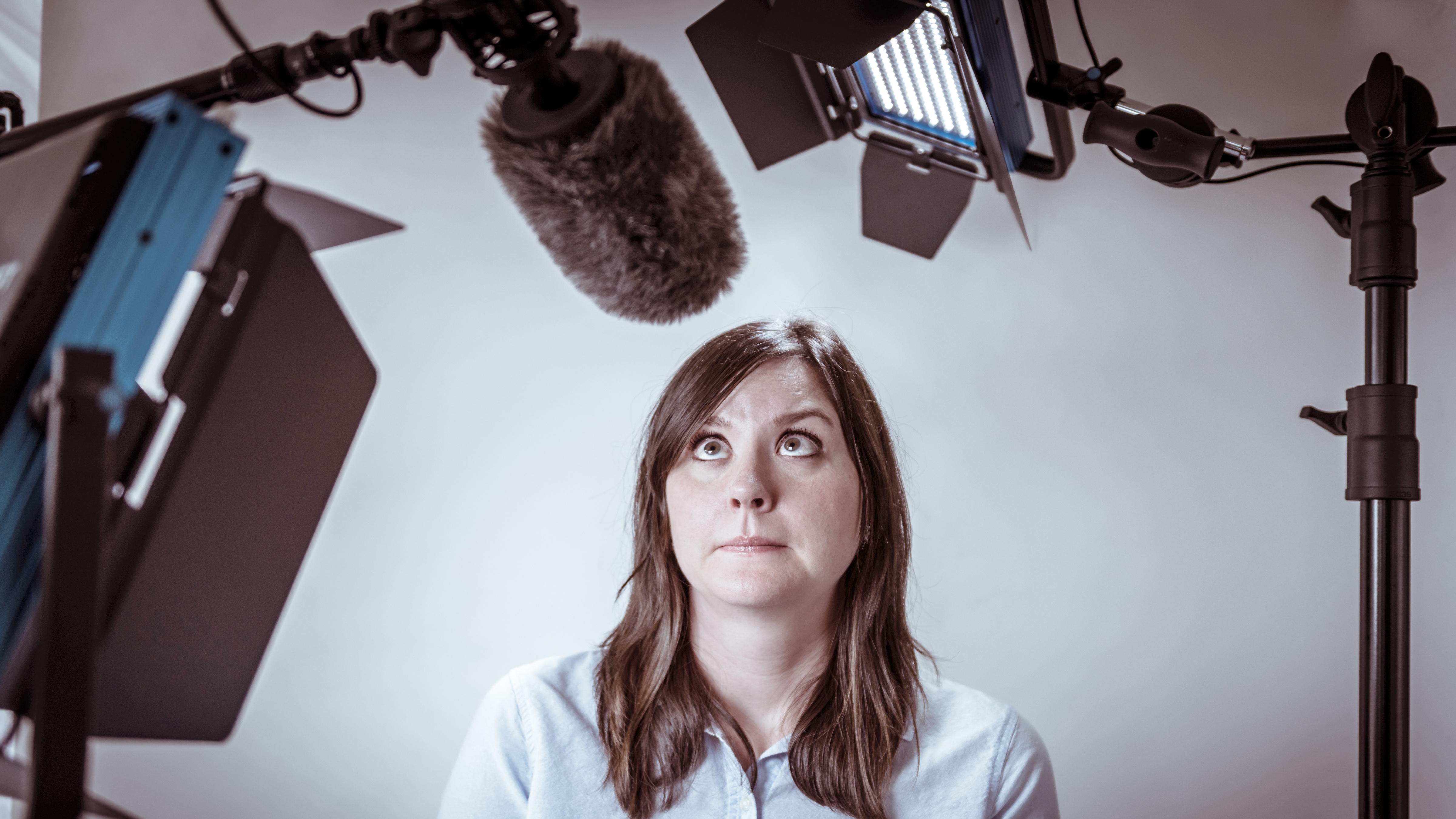 Woman looking worried at camera equipment that includes a microphone, lighting, and camera