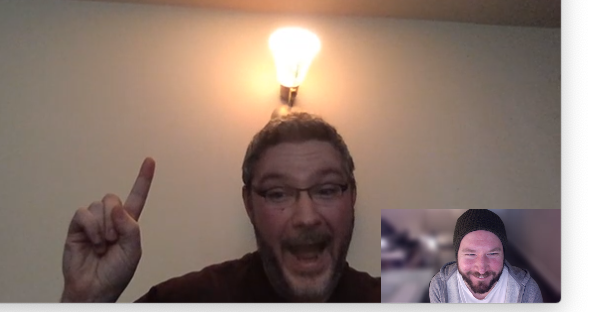 Zoom video chat between two men with one man smiling and pointing to a lightbulb above his head