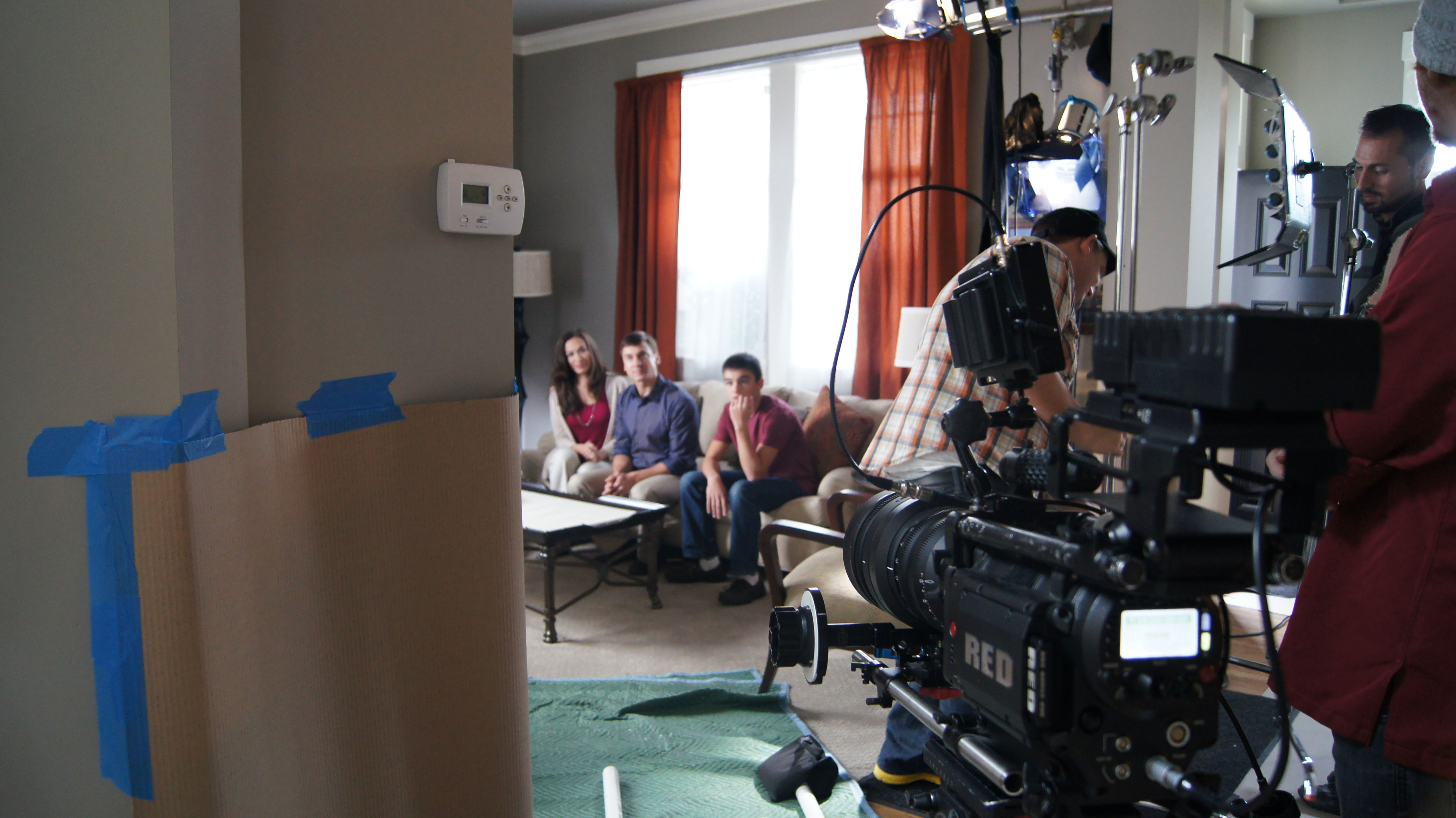 Video production crew filming two parents and a child in a living room setting