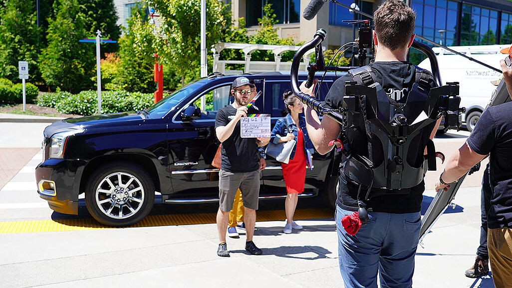 Video production company filming live-action video outside in front of a car