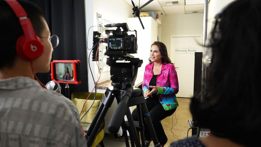 Behind the scenes look of a woman being interviewed on-camera