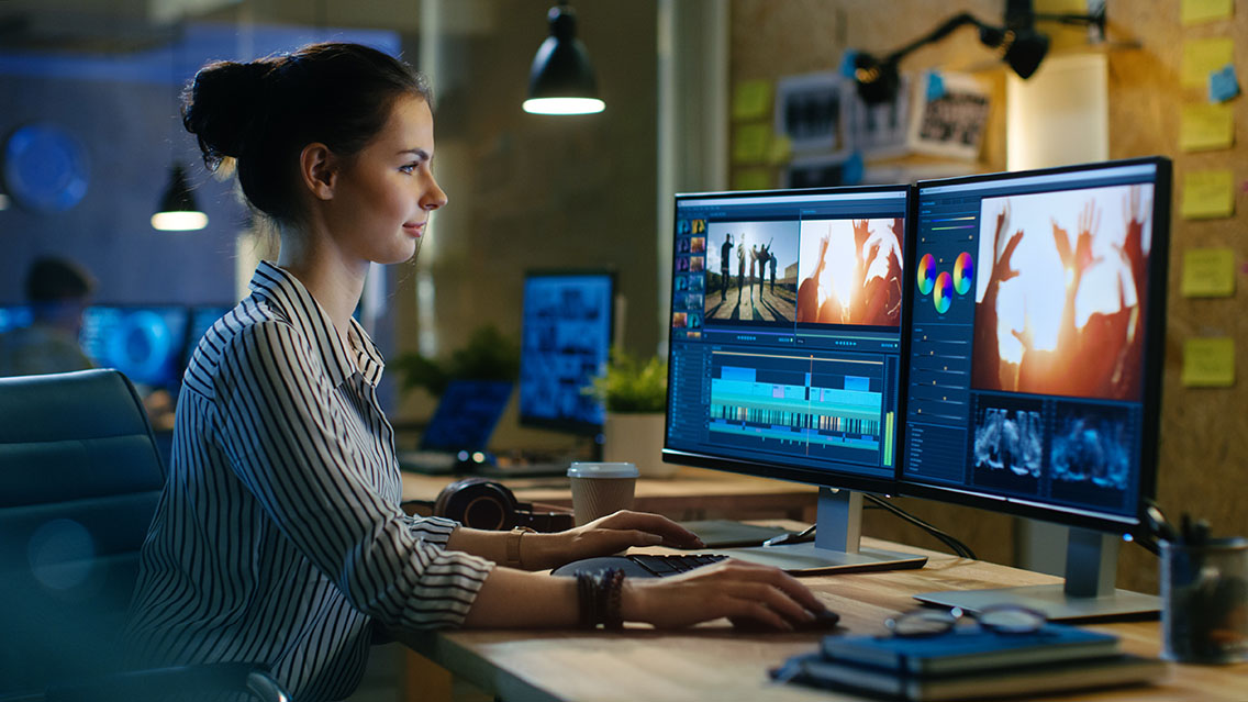 Woman editing a video in its post-production stage on two computer monitors