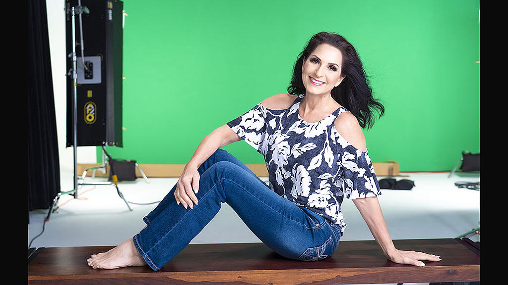 CEO of VMG Studios, Kelly Sparks, sitting on a bench in a studio with a green screen and video production equipment in background